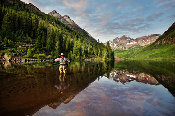 USA, Colorado, Pitkin County, Angler on Maroon Lake reflecting Maroon Bells