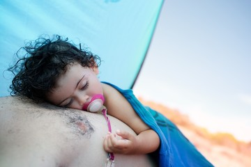 Girl (2-3) sleeping on father's chest