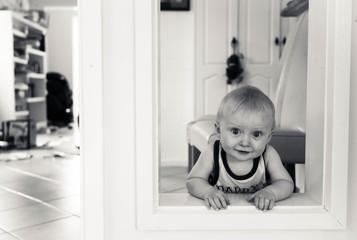 Australia, Canberra, Hackett, Baby boy (6-11 months) playing peekaboo around door frame