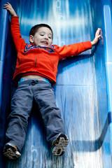 Boy (2-3) on playground slide