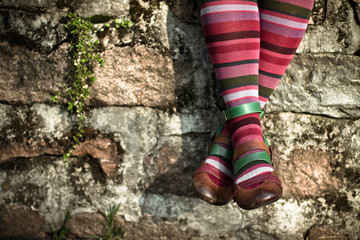 Italy, Lombardy, Milan, Woman wearing striped socks while sitting on wall