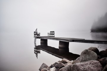 Sweden, Dalarna, Pier reflecting in surface of water in misty, foggy morning