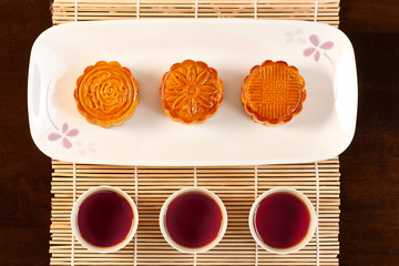 Three cups of tea and three mooncakes served on white plate