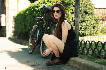 Italy, Lombardy, Milan, Woman sitting next to bike
