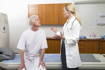 Female doctor talking to male patient next to MRI Scanner