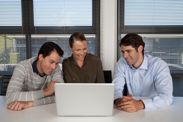 Three businesspeople looking at laptop in the office