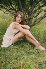 Teenage girl (14-15) sitting under tree