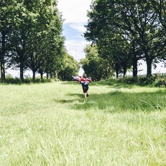 Boy running through field with Union Jack flag
