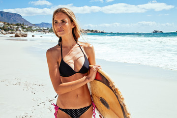 Young woman on the beach with surfboard underarm