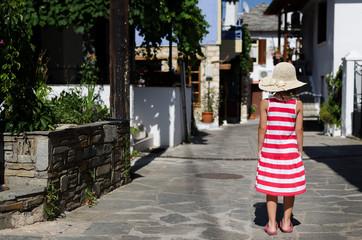 Greece, East Macedonia and Thrace, Thasos, Girl (4-5) walking through village