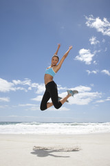 Young woman jumping on beach