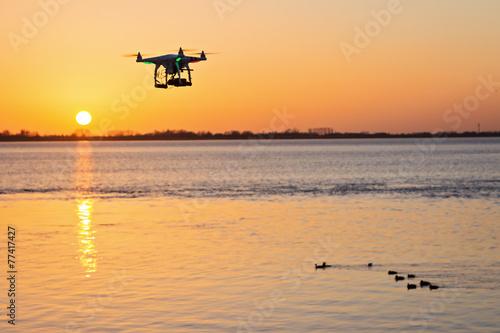 Fliegende Kameradrohne vor Sonnenuntergang - 77417427