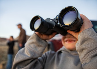 Young boy looking through large set of binoculars