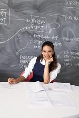 Businesswoman sitting by blackboard in the office