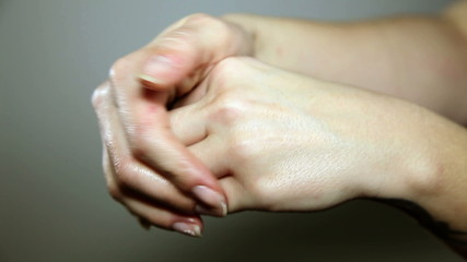 Close up shot of a woman`s hands spreading a cream ower the fingers
