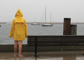 Back view of woman warring yellow raincoat during hurricane
