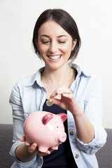 Young Woman dropping coin in piggy bank