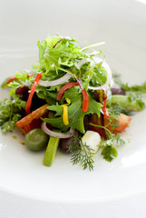 Fresh salad with vegetables and fruits on white plate