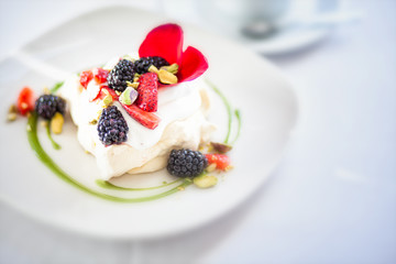 Merangue topped with cream and fresh fruit
