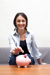 Young woman dropping coin into piggy bank