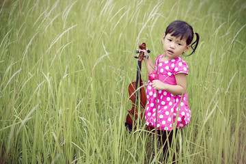 Girl holding violin in meadow