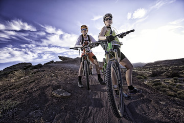 USA, Colorado, Mesa County, Grand Junction, Man and woman standing with mountain bikes on trail