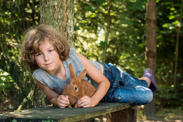 Boy (6-7) holding pet rabbit and lying down on bench in forest