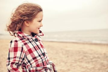 Small girl (2-3) in coat on beach