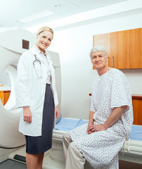 Female doctor and male patient next to MRI scanner