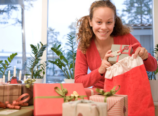 Woman putting Christmas gifts in sack