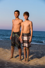 USA, North Carolina, Dare County, Nags Head, Portrait of two boys (12-13) on beach at sunset