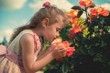 Girl (4-5) smelling flower