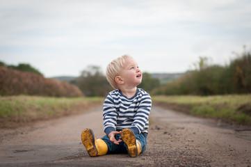 Boy sitting on path
