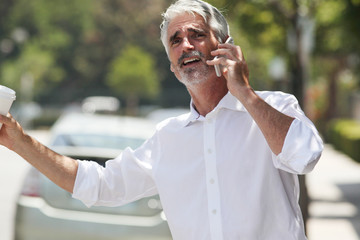 Businessman trying to hail cab while talking on phone