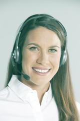Woman wearing headset, smiling