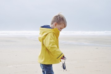 Boy in raincoat on beach holding mussels