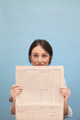 Young woman holding up financial newspaper