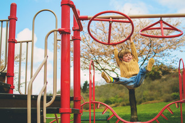 Boy  (4-5) hanging from playground climbing frame and  laughing