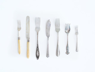 A set of vintage dining knifes and forks of different shapes and