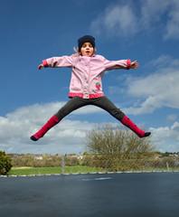 Preschool girl (2-3) jumping on trampoline
