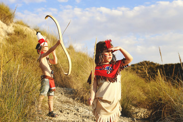 Girl (6-7) and boy (4-5) playing dressed as Indians