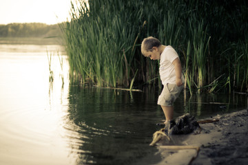 Portrait of boy testing the water of calm pond with leg