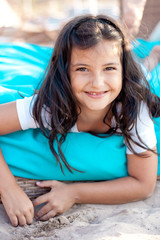 Happy smiling girl (6-7) lying on sand on beach