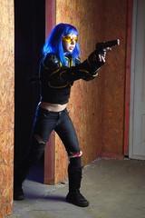 Beautiful girl with blue hair holding gun in strikeball location