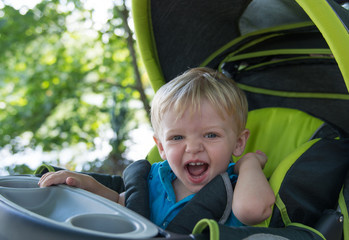 Toddler boy laughing while riding in stroller