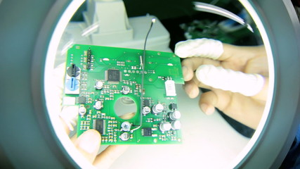 Precision quality control checks Chinese worker PCBs, China