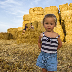 Three children playing on field of hay bales