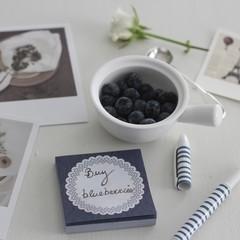 Blueberries in bowl beside hand written memo