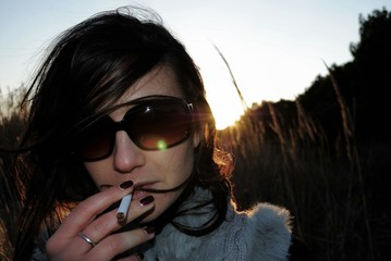 Young woman smoking at sunset
