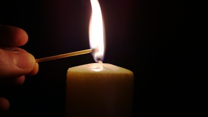 Match lighting candle in dark